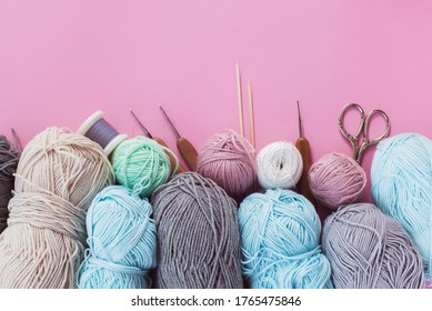 Women's hobby. Multicolored skeins, needles, hooks on the yellow  background. Concept of sewing, crochet and knitting.
