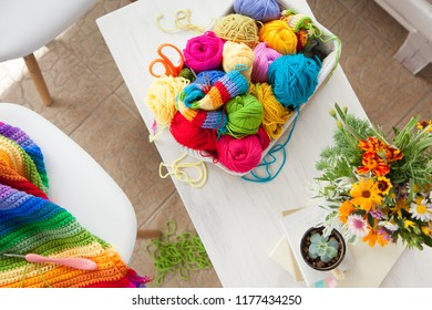 Women's hobby. Needlework and crocheting and knitting. Bright yarn in the basket. Concept of women's leisure.