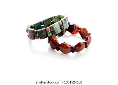 Women's jewelry. New, female jasper and carnelian bracelets on a white background close-up