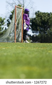 Women's lacrosse goal keeper with grass in the foreground allowing drop-in text