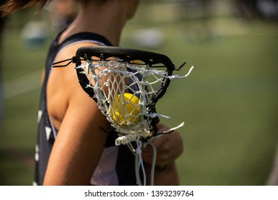Women's lacrosse player holding a lacrosse ball in their lacrosse stick.