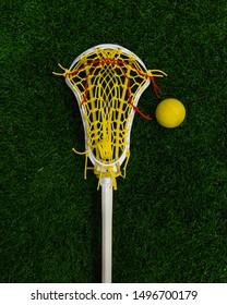 Women's lacrosse stick and ball laying on turf lacrosse field.