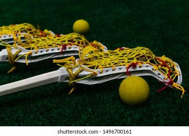 Women's lacrosse sticks and balls laying on turf lacrosse field.