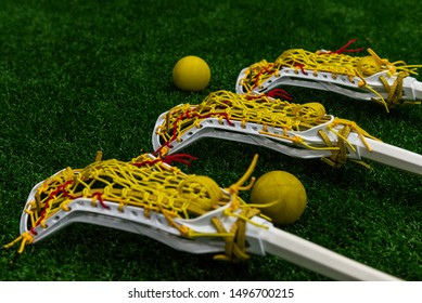Women's lacrosse sticks and balls laying on turf lacrosse field.