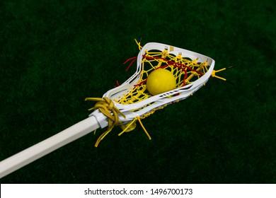 Women's lacrosse sticks holding a lacrosse ball on a lacrosse field.