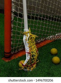 Women's lacrosse sticks leaning against a lacrosse net with yellow lacrosse balls.