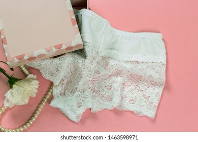 Women's lacy panties and perl necklace as a gift on pink background. Top view.
