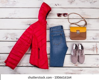 Women's late autumn look idea. Combination of red down jacket and jeans completed with sneakers, shoulder bag and sunglasses.