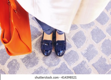 Women's legs in dark blue shoes. Bright orange handbag. Light brown coat, orange classic hand bag and dark shoes. Street fashion, Street style. Business casual look. Autumn outfit.