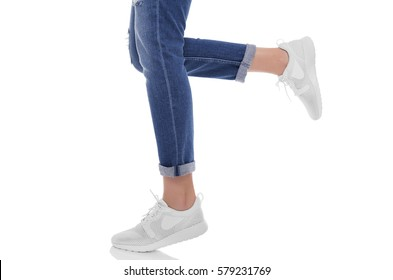 Women's legs in jeans and sneakers. Isolated on white background.