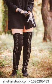 Women's legs in long ankle boots with lace-ups