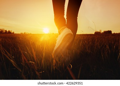Women's legs on the meadow walking concept