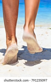 Women's legs on a sandy beach, Maldives