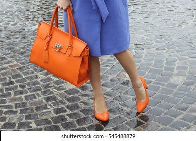 Women's legs in orange shoes. Bright orange shoes and handbag. Stylish slim  girl in soft blue warm coat, gray warm dress and heels walking on the rainy wet street.