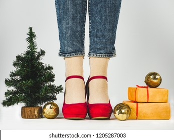 Women's legs in stylish, pink shoes, gifts with a red ribbon, gold balls and a Christmas tree. White background, isolated, close-up. Preparing for the holidays