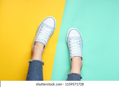 Women's legs in tight, torn jeans, sneakers on yellow blue pastel background. Top view, minimalism, copy space