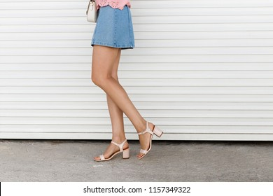 Women's legs. Woman wearing blue denim mini skirt and pink block heeled sandals walking near white roller door. Details of trendy casual outfit. Everyday look. Street fashion.