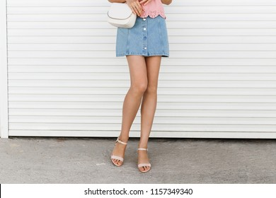 Women's legs. Woman wearing denim mini skirt, pink block heeled sandals, cross body bag with chain strap walking near white roller door. Details of trendy casual outfit. Everyday look. Street fashion.