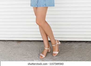 Women's legs. Woman wearing denim mini skirt and pink block heeled sandals walking near white roller door. Details of trendy casual outfit. Everyday look. Street fashion.