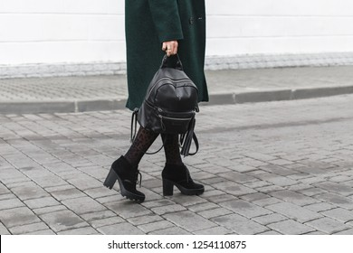 Women's legs. Woman wearing midi green coat, black chunky heeled boots, backpack, leopard print tights walking on the city streets. Trendy casual outfit. Details of everyday look. Street fashion.
