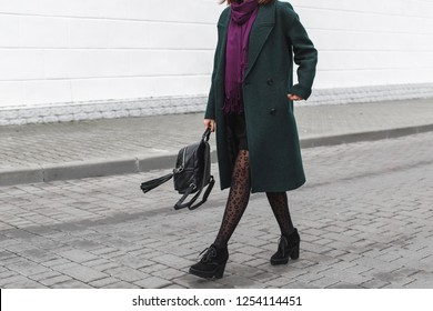 Women's legs. Woman wearing midi green coat, black heeled boots, backpack, leopard print tights, purple scarf walking on city streets. Trendy casual outfit. Details of everyday look. Street fashion.