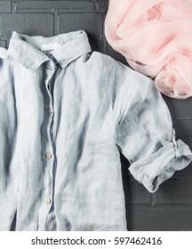 Women's linen shirt on a black background, silk scarf, soft focus, vertical