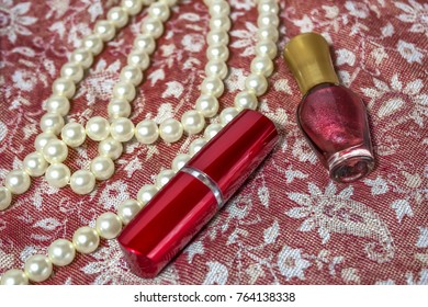 Women's lipstick, necklace, nail Polish on fabric with Oriental ornaments
