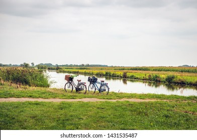 Women's and men's bicycle, each with a basket on the handlebars,  parked along the water of a stream in a Dutch polder. The owners are not visibly present in the area.