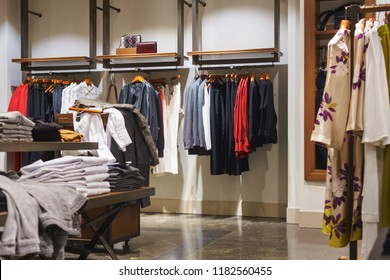 Women's and men's outerwear on hangers and shelves in a modern clothing store. Shopping and sale. The clothing store.
