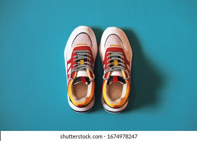 Women's multi-colored sneakers on a turquoise background.