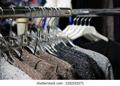 Women's new sweaters hanging on hangers. Only big sizes XL to XXXL. Horizontal close up image.