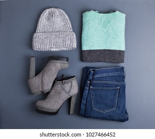 Women's outfit. Fashion clothes and accessories in pastel colors on gray background. Flat lay, top view.