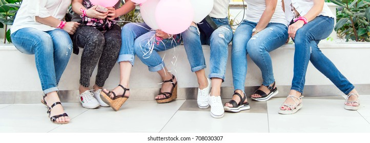 Women's party before the wedding. Birthday party. Women in shopping center wearing jeans and t-shirts. Cheerful walk with girlfriends. Group of six woman leg sit on bench.