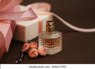 Women's Pink Perfume in Beautiful Bottle and Artificialt Flowers Bracelet on Brown Background with gift boxes on Background.
