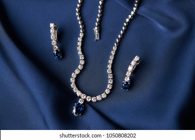 Women's platinum necklace and earrings with a diamond and blue precious sapphire stone on a silk blue background, close-up. Luxury female jewelry