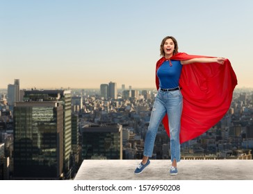 women's power and people concept - happy woman in red superhero cape over tokyo city skyscrapers background