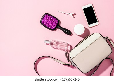 Women's QUILTED CROSSBODY BAG with a long handle and accessories, phone, comb, perfume, cream on a pink background. Banner. Concept of fashion and beauty, modern, stylish. Flat lay, top view