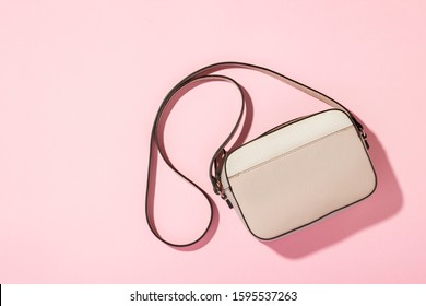 Women's QUILTED CROSSBODY BAG with a long handle over his shoulder on a pink background. The concept of fashion and beauty, modern, stylish. Flat lay, top view