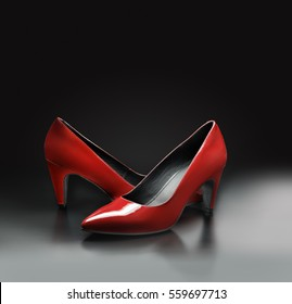 Women's red leather pumps shoes on grey background.