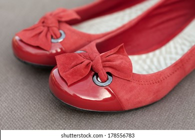 Women's red shoes with bows against a brown material background.