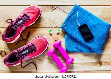 Women's running shoes and dumbbells for training