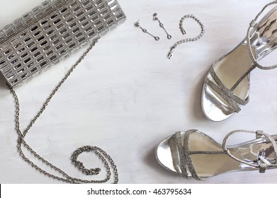Women's set of fashion accessories in silver color on wooden background: shoes, handbag and jewelry