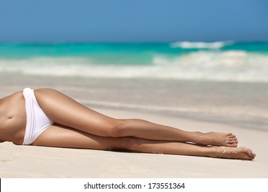 Women's sexy legs on the beach