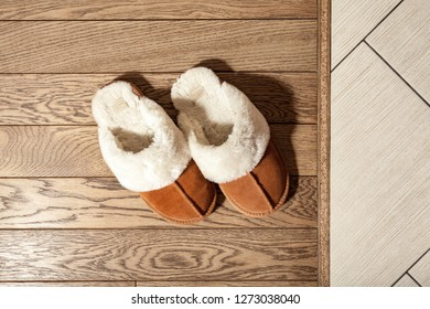 women's shoes on the floor in the apartment. Shoes with heels spoils the parquet floor made of natural wood.