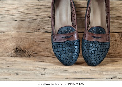 Women's shoes on a wooden background closeup. Blue summer women's shoes. Free space for text. Copy space.