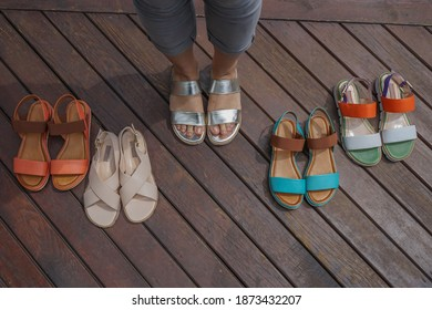 Women's shoes on the wooden floor. Shoes laying on the floor. A lot of different shoes.