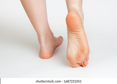 Women's smooth and beautiful feet, on a white background. The soles of the feet close up. Cosmetology and medicine