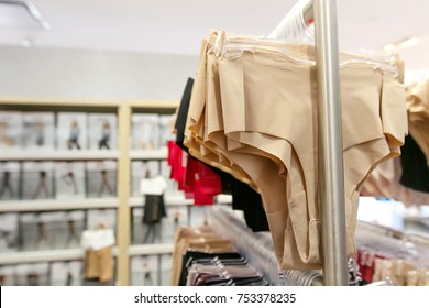 Women's spanx underwear hangs on a rack for sale at a department store.