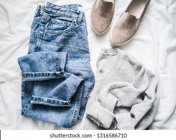 Women's spring clothes - mom's jeans, gray pullover and suede sneakers on a light background, top view