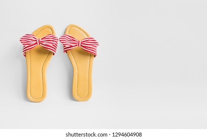 Women's stripy bow sandals on white background with copy space for text.